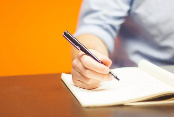 A man's hand is holding a pen and it is poised over a pad of paper